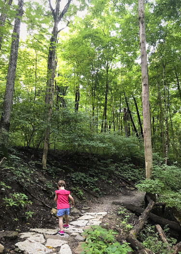 Girl hiking on trail in the woods.