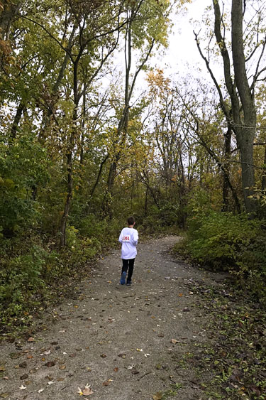 Boy running on trail at nature preserve.