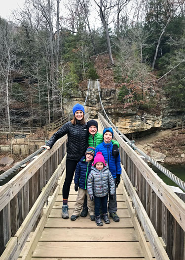 Family standing on a wooden swing bridge