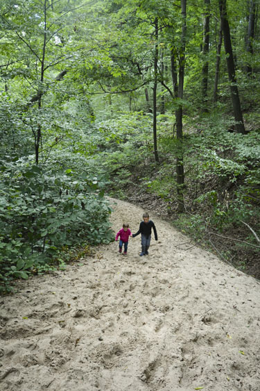 Sister and brother hiking up sandy trail at Warren Dunes.