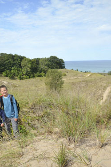 Family of four siblings standing on sand dune at Warren Dunes.