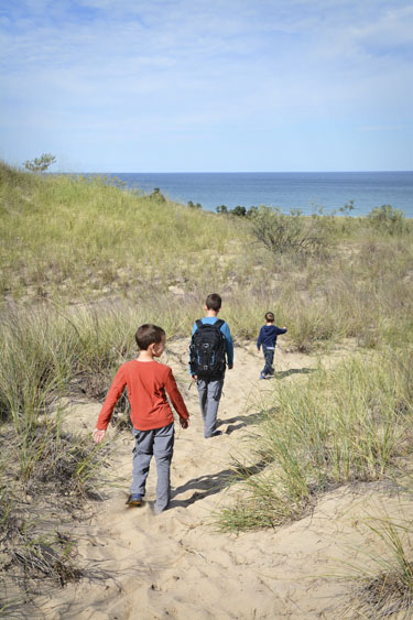 Three brothers hiking over sand dunes.