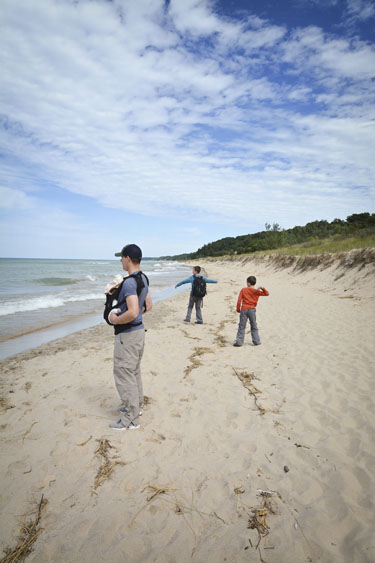 Two boys skipping rocks along Lake Michigan shoreline while father and baby watch.