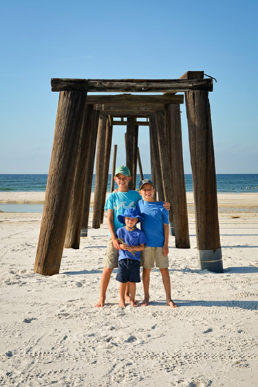Three brothers standing on the beach in front of old pier.