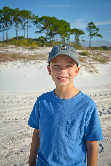 Boy smiling on the beach.