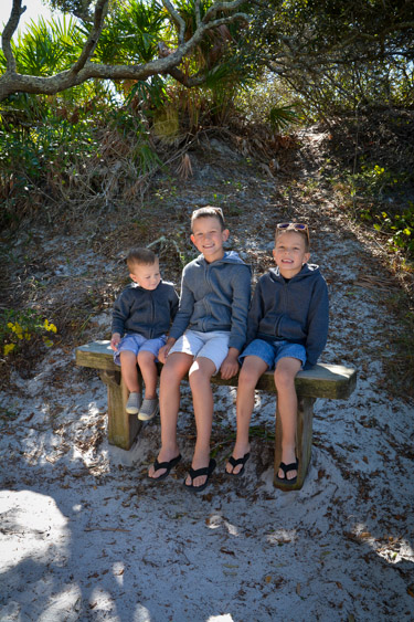 Three brothers sitting on a bench on a beach nature trail.
