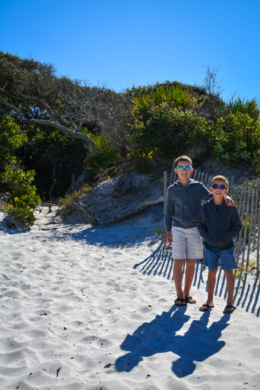 Two brothers standing on a beach.