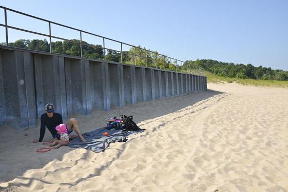 Father and baby sitting in the shade on Warren Dunes State Park beach.