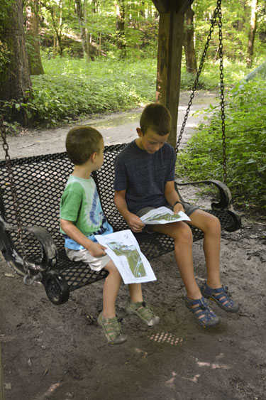 Boys sitting on a bench swing at Cool Creek Nature Preserve