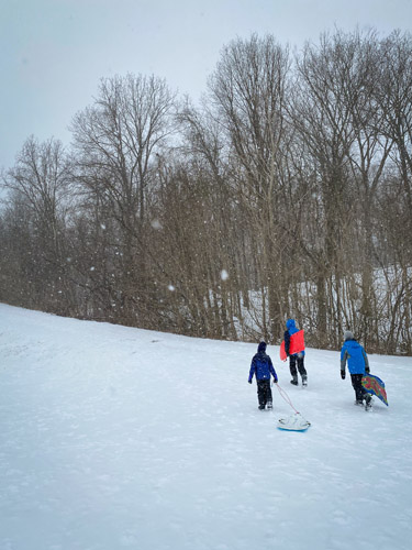 Three boys walking up the sledding hill at Fort Harrison State Park.