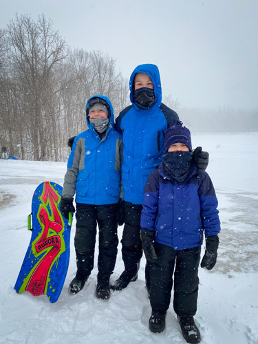 Three boys ready to go sledding at Fort Harrison State Park.