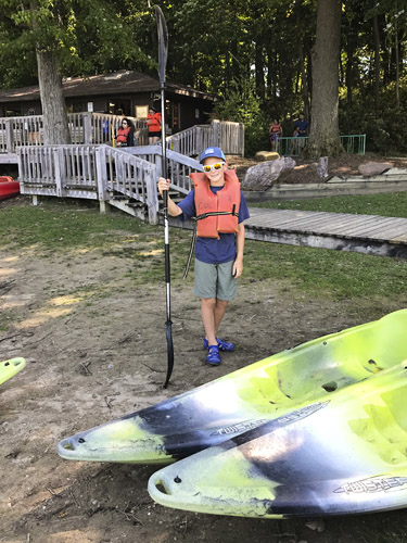Boy standing with paddle beside kayaks at Chain O' Lakes boat rental