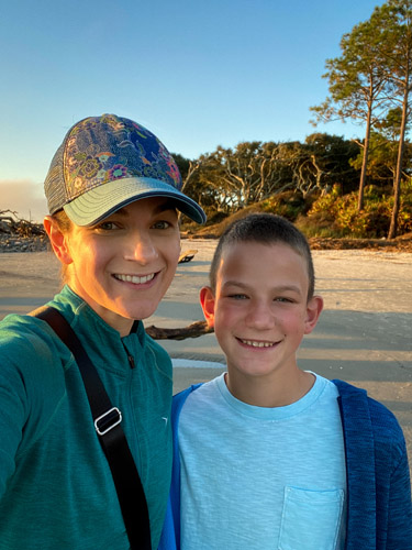 Mom and son at the beach at sunrise.