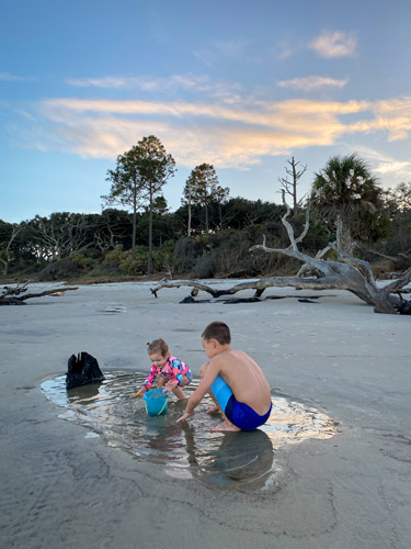 Young girl and boy playing in a tide pool at Driftwood Beach at dusk.