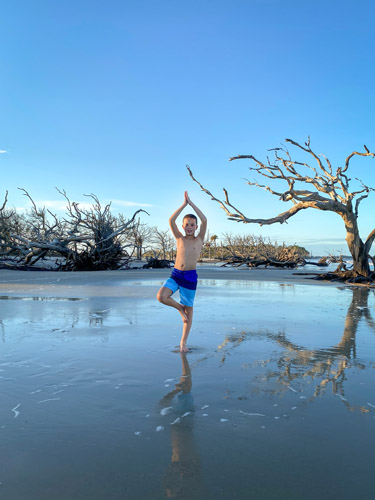 Boy doing a yoga pose on Driftwood Beach at sunset.