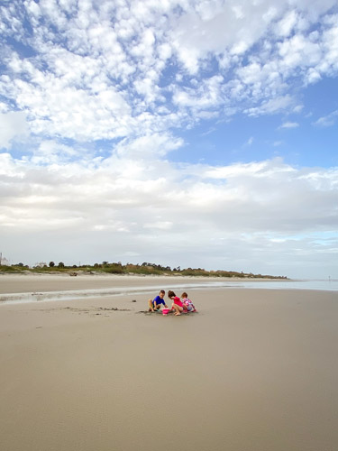 Three young kids playing in the sand at Jekyll Island's Great Dunes Beach Park.