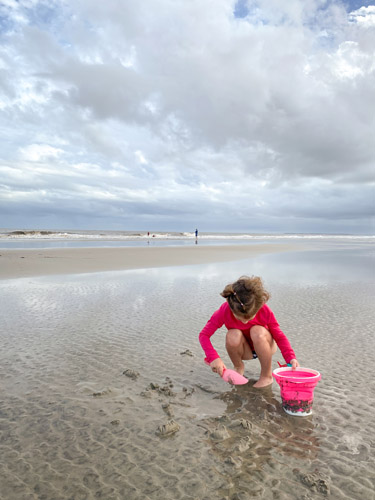 Young girl digging in the sand at Jekyll Island's Great Dunes Beach Park.