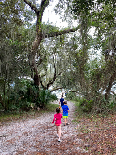 Kids walking through trees to reach St Andrew's Beach West