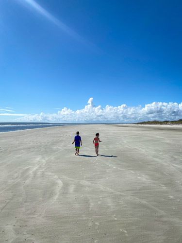Two young kids walking on St Andrews Beach East.