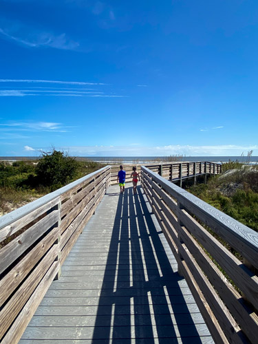 Two young kids walking on the wooden walkway toward St Andrews Beach East.