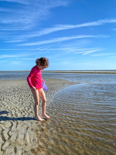 Girl dipping her toe in the water at St Andrews Beach East on Jekyll Island.