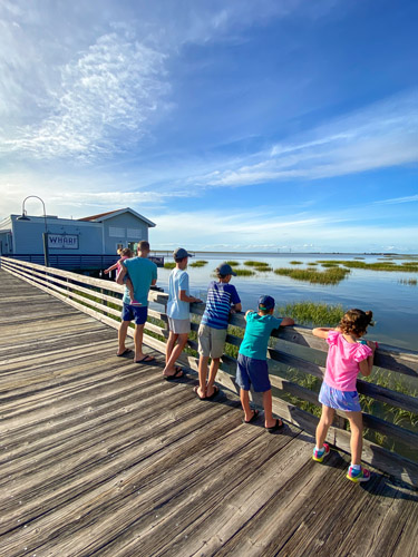 Family of six looking out at the water from the Jekyll Island Wharf.