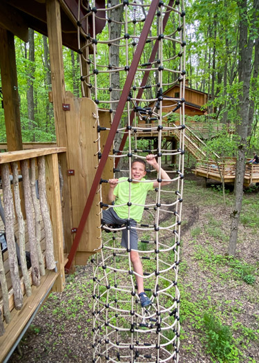 Boy climbing the rope ladder to the Drey Hammock Platform in the Cannaley Treehouse Village.