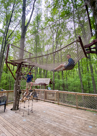 Two boys playing on a net structure above a tent platform in the Cannaley Treehouse Village.