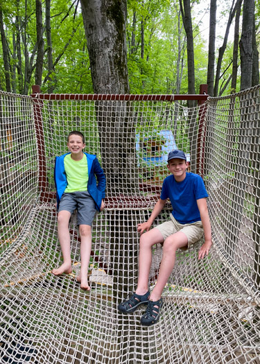 Two boys sitting in net structure above a tent platform in the Cannaley Treehouse Village.