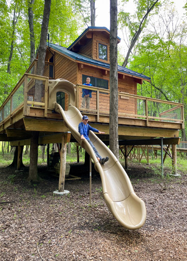 Boy sliding down the slide from the Hub Treehouse at the Cannaley Treehouse Village in Oak Openings Metropark.