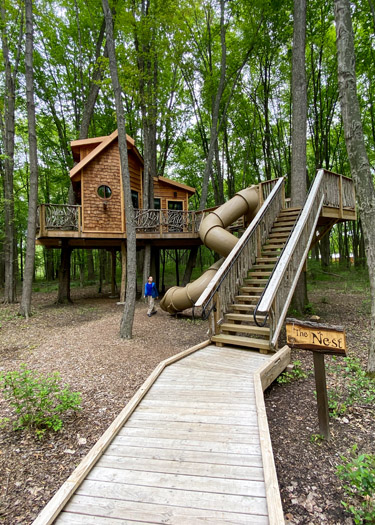 Boy standing at the bottom of the slide from the Nest Treehouse at the Cannaley Treehouse Village in Oak Openings Metropark.