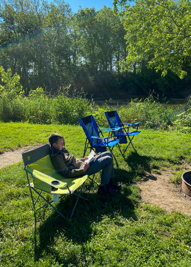Boy reading by the firepit at campsite.