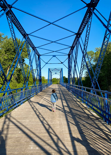 Girl walking on the bridge between the White River Campground and Koteewi Park.