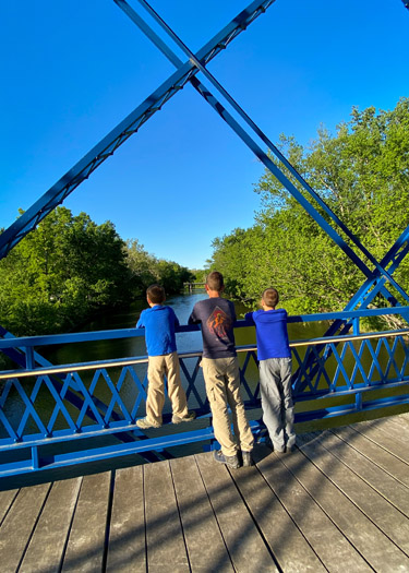 Three boys looking over the bridge at the White River Campground.