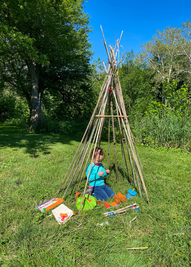 Girl playing inside stick teepee at campsite.