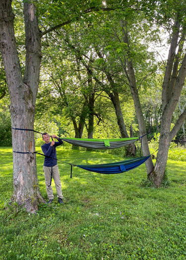 Boy hanging up two hammocks at campsite.