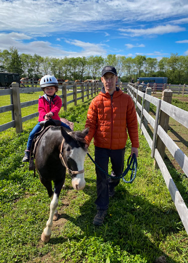 Dad leading girl on pony ride.