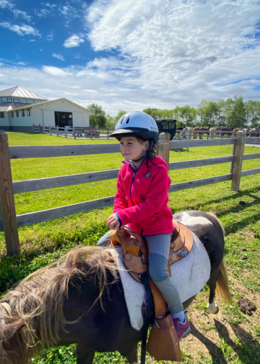 Young girl riding on pony at K-Trails Equestrian Center