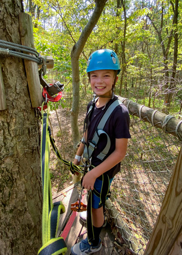 Boy waiting to being ropes course at Koteewi Aerial Adventures.