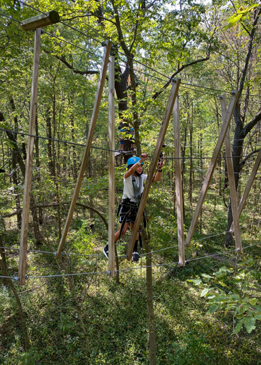 Boy walking on ropes course at Koteewi Aerial Adventures.