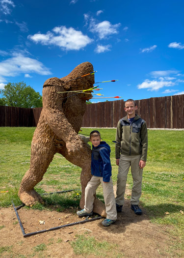 Two boys standing in front of bigfoot target at Koteewi Archery Range.