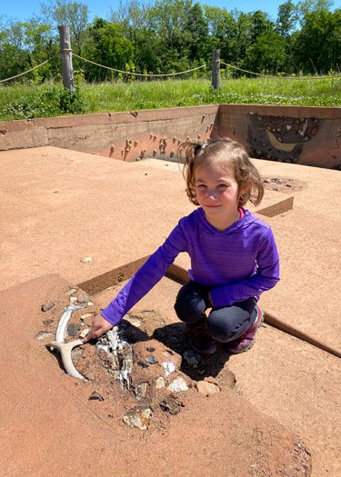 Girl examining faux archeology site at Koteewi's Taylor Center for Natural History.