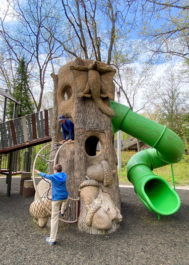 Two boys climbing inside a play structure resembling a tree trunk.
