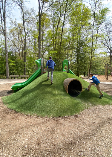 Boys playing on a terra-formed play structure at the Oak Openings Mallard Lake Playground.