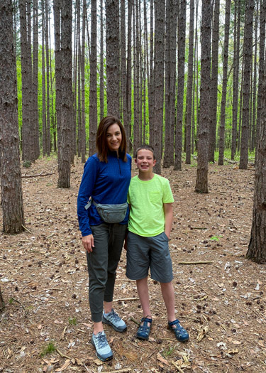 Mom and son standing in pine forest.